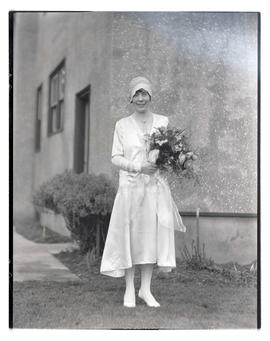 Unidentified bride outside building, full-length portrait