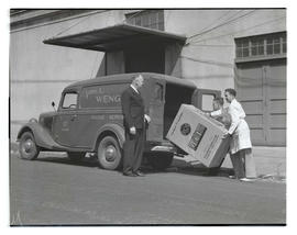 Two people loading RCA Victor radio into Vern L. Wenger Radio Service truck