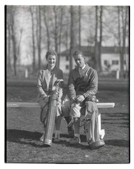 Two golfers seated on bench