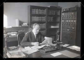 Unidentified man sitting at desk and reading documents