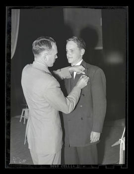Unidentified man receiving pin from U. S. serviceman