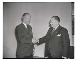 R. G. Barnett and Gordon J. Malone shaking hands during conference for gas company executives