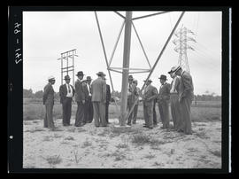 Men in field with transmission lines