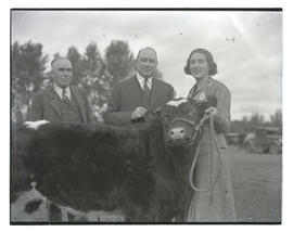Three people posing with steer