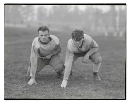 Two football players posing on field