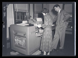 Man and woman with accounting machine