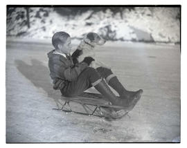 Unidentified boy and dog on sled