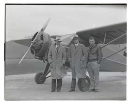 Three unidentified men with monoplane