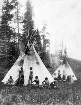 Blackfeet Indian people at two skin lodges, Montana, circa 1907