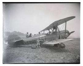 Boy posing with biplane, Rose O'Portland, as Tex Rankin watches from cockpit