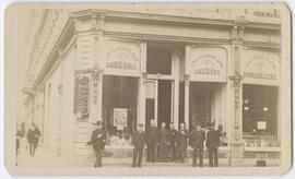 Group of unidentified men in front of C. W. Cornelius storefront, Portland, Oregon
