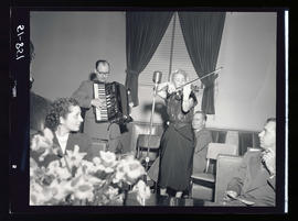 Man and women playing accordion and violin with microphone