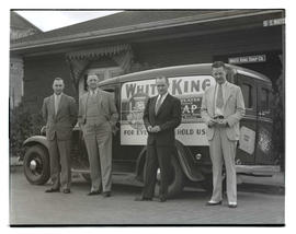 Four men posing with truck outside White King Soap Company office, Portland